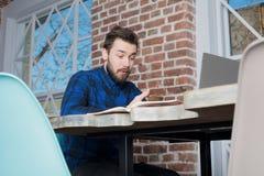 在手机的惊奇的年轻行家人读书正文消息在便携式计算机上的工作期间 免版税图库摄影