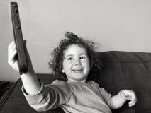 在手机的愉快的儿童女孩戏剧 库存图片
