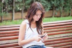 在手机的懊恼女孩键入的消息 免版税库存照片