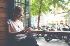 在手机的有吸引力的妇女读书正文消息,当坐在舒适咖啡店时 免版税库存图片