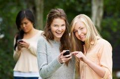 在手机的正文消息被胁迫的十几岁的女孩 库存图片