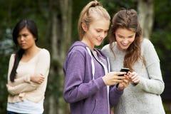 在手机的正文消息被胁迫的十几岁的女孩 库存照片