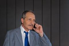 在手机的生意人 免版税库存照片