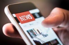 在手机的网上新闻 关闭智能手机屏幕 免版税库存图片