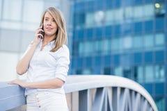 在手机的美丽的女性商业主管在现代城市 免版税库存照片