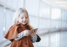 在手机的被集中的小女孩观看的动画片 库存图片