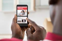 在手机的非洲人读书新闻 库存图片
