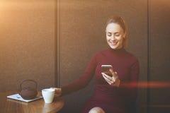 在手机的年轻人微笑的女性读书正文消息,当休息在咖啡店内部时 库存照片