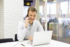 在手机的年轻商人在办公室 库存照片