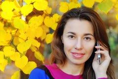 在手机的年轻秀丽妇女文字消息在秋天同水准 免版税库存图片