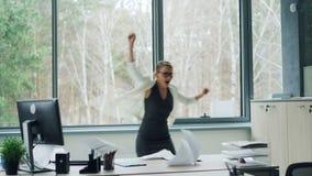 在手机谈话然后跳舞和叫喊投掷的纸庆祝喜讯的女性办公室工作者 成功 影视素材