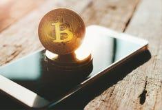 在手机隐藏货币背景c的金黄bitcoin硬币 库存照片