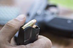 在手枪夹子关闭的装载9mm弹药 手、子弹、杂志和手枪 库存图片