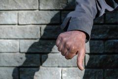 在手标志下的拇指 姿态反感和阴性的人的手 分歧,憎恶的概念,不快乐 在灰色的特写镜头视图 免版税库存图片