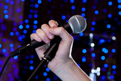 在手歌手的话筒 免版税库存图片
