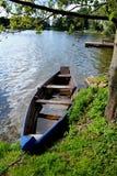在手段湖海岸附近的老木蓝色小船 免版税库存照片