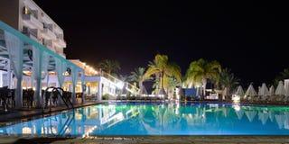 在手段的水池在夜间的旅馆与照明 免版税图库摄影