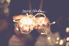 在手的圣诞快乐发光的词有党光串的 免版税库存照片