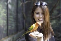 在手边享用与爱鸟和身体的亚裔美女 库存图片