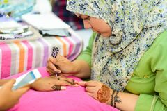 在手边做mehndi艺术设计的回教妇女 免版税图库摄影