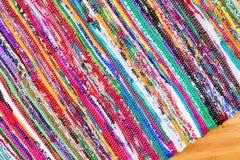 在手边关闭被编织的五颜六色的地毯在角度 库存照片
