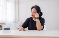 在手边坐在木桌休息下巴的亚裔妇女有喜怒无常的e的 免版税库存图片