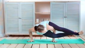在手边实践瑜伽身分的灵活的妇女做平衡全景 股票视频