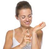 在手边应用香水的愉快的少妇 免版税库存图片