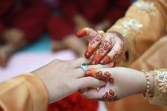 在手边投入金戒指的夫妇 免版税图库摄影