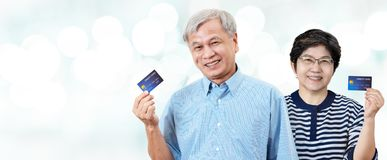 在手边拿着信用卡的愉快的资深亚裔父母画象微笑和看照相机 库存照片