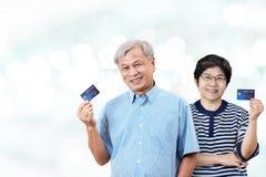 在手边拿着信用卡的愉快的资深亚裔父母画象微笑和看照相机 免版税图库摄影
