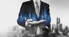 在手边拿着蓝色现代大厦全息图,有黑白城市背景的商人 免版税库存图片