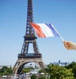 在手边显示在埃佛尔铁塔前面的特写镜头旗子在巴黎 免版税库存照片