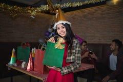 在手边显示绿色礼物袋子的美丽的女服圣诞老人帽子在餐馆 圣诞晚会的概念和新年集会 库存照片