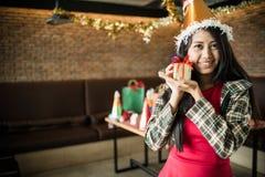 在手边显示金黄礼物盒的美丽的女服圣诞老人帽子在餐馆 圣诞晚会的概念和新年集会 免版税库存照片