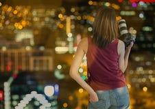 在手边有照相机的摄影师在城市在晚上以被弄脏的光和bokeh交叠 免版税库存照片
