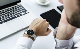 在手边检查时间手表的人特写镜头 库存图片
