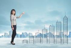 在手边爬上被画的大厦的女商人在城市 免版税库存照片