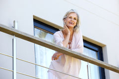在手边站立在大阳台的有吸引力的老妇人休息的头 免版税库存照片