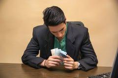 在手边计数现金的坐的年轻商人 免版税库存图片