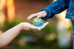 在手边给小女孩地球的人 免版税库存图片