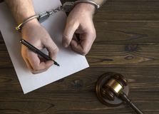 在手铐和法官的锤子的手 免版税图库摄影