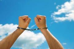 在手铐束缚的人的手,在蓝天的背景 免版税图库摄影
