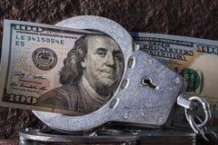 在手铐特写镜头的100美元 在美元循环的局限的概念用不同的国家 库存图片
