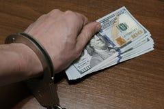 在手铐的一只人` s手在一张坚果色桌的表面放置一盒一百美元票据 违反法律, corrup 库存照片