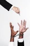 在手铐的商人和妇女递解决公共汽车的提供的钥匙 免版税库存图片