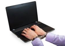 在手铐的手在膝上型计算机 免版税库存图片