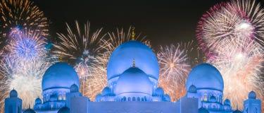 在扎耶德在日落阿布扎比,阿拉伯联合酋长国的Grand Mosque回教族长上的美丽的烟花 图库摄影