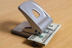 在打孔器的纸钞票纸的 浪费一家大公司的企业概念 免版税库存照片