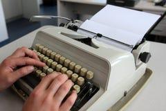 在打字机的妇女文字 免版税库存图片